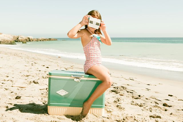 girl sitting on coolbox on beach looking through royalty free image 1596796445 Ingrosso Casalinghi da oltre 50 anni
